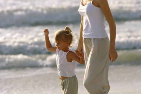 Daughter walking down beach with mother