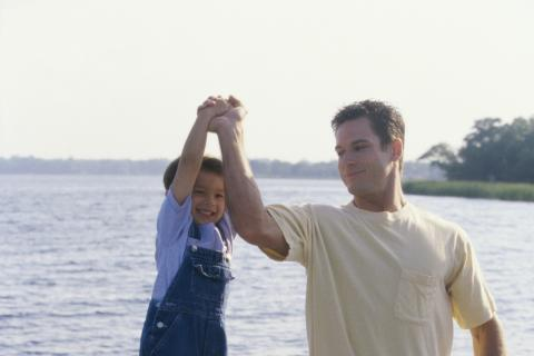 Dad lifting son with one arm on a dock