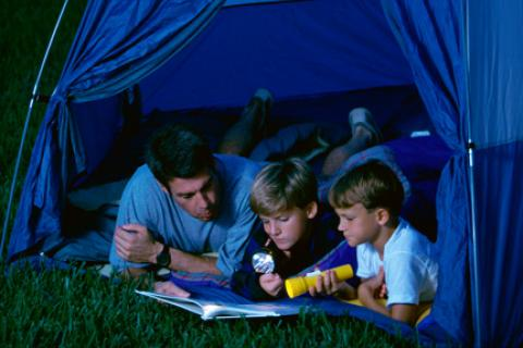 Dad and sons camping in the backyard