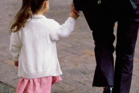Little girl walking hand in hand with mother