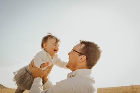 Father holding laughing baby daughter
