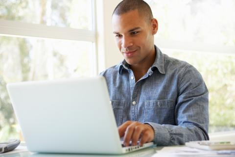 Man sits at table while using a laptop