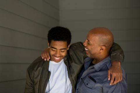 Teenager son and father stand laughing, arms around each other's shoulders