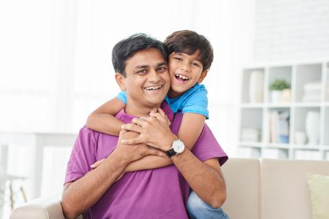 Smiling son hugs doting father from behind