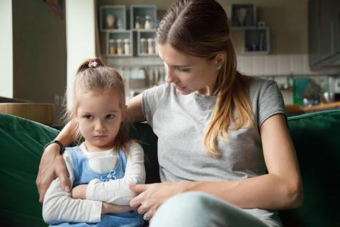 Mom consoles upset daughter on couch.