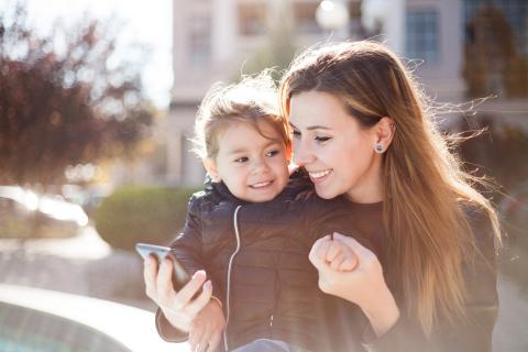Mother holds child's hands as she looks at her phone outside on a crisp Autumn day.