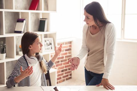 Mother and daughter having heated argument at kitchen table