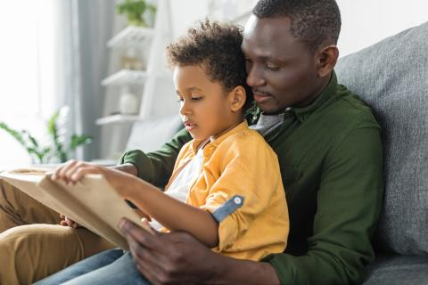 Father holds son in lap on the living room couch while they read their favorite book together.