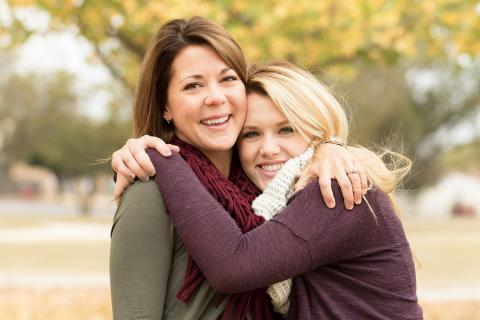 Mother and adult daughter embrace outside on a fall day
