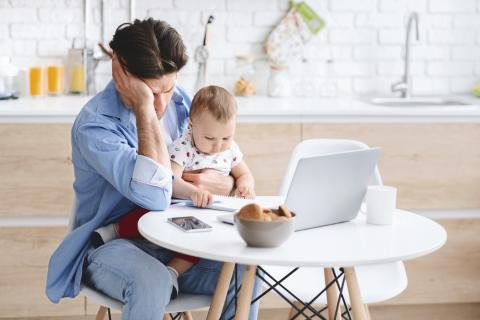 Man sits at his computer desk holding his baby with a disappointed look on his face.