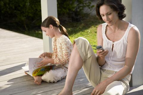 Mother and daughter sit together on a porch while Mother looks at her phone.