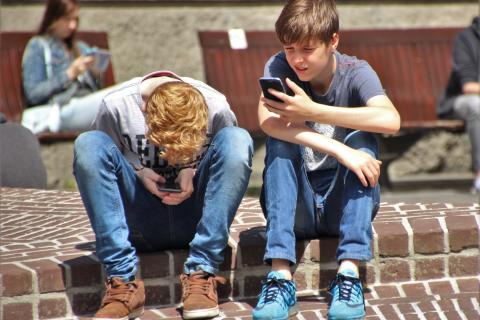 Two boys sit on a step and look at their smartphones.