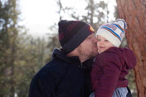 A father kisses his child in the woods on a chilly day.