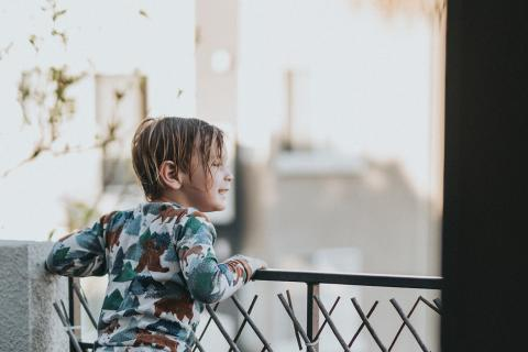 Little girl looks at her neighborhood from the balcony of her family's apartment.