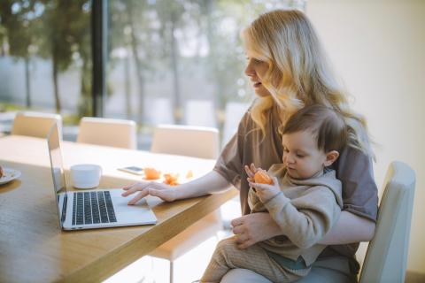 Mom sits down to work on her computer with her child eats a snack while sitting on her lap.
