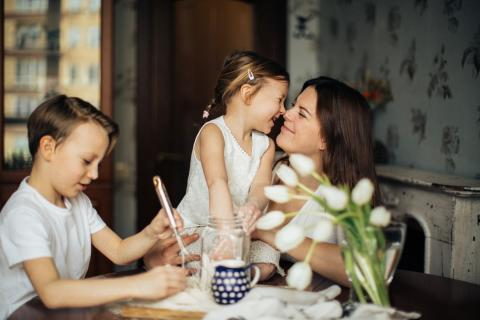 A mother shares a loving moment with her kids at the table.