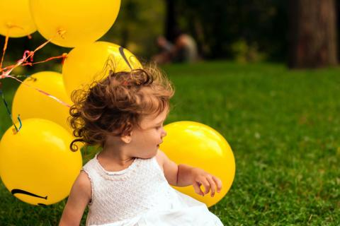 Young girl sits in the grass with a bunch of yellow balloons