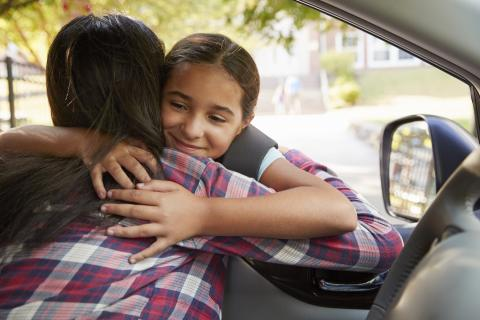 Daughter and mother hug to greet each other in the car.