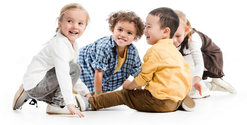 A group of smiling children sit on the floor playing