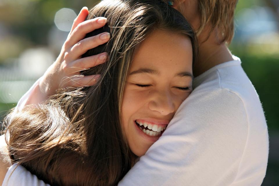Smiling teenager is hugged close by parent
