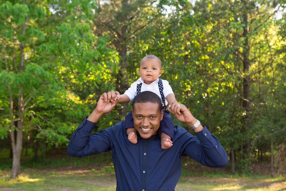 Father carries baby on shoulders outside