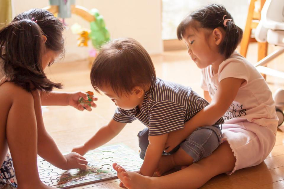 Siblings sit on the floor of their playroom while working on a puzzle together.
