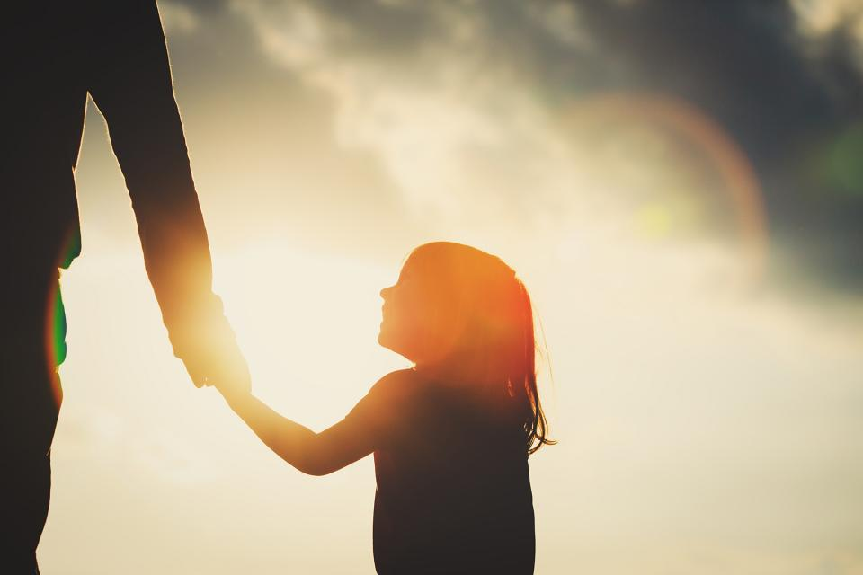 Silhouette of young girl looking up lovingly at parent while holding their hand.