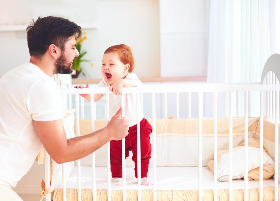A father plays with his infant child on the side of the crib.