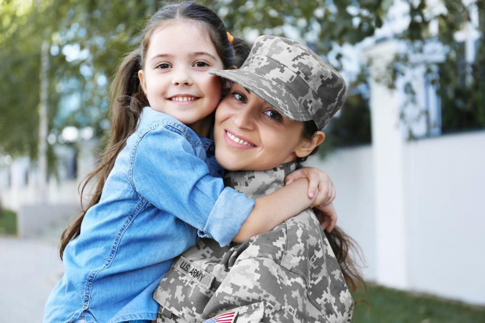 A military mother greets her daughter with a smile.