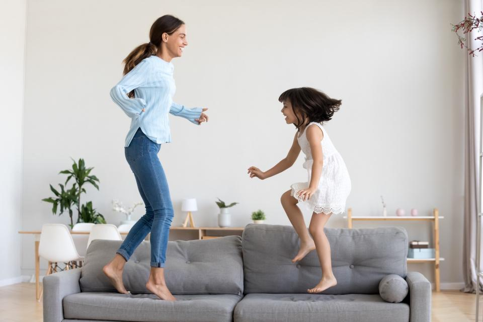 A girl and her mother play together in the living room.