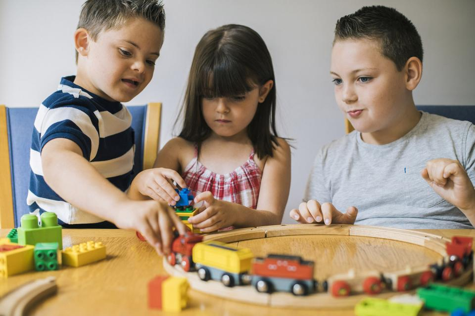 Three siblings sit at an activity table and play with a heap of educational toys.