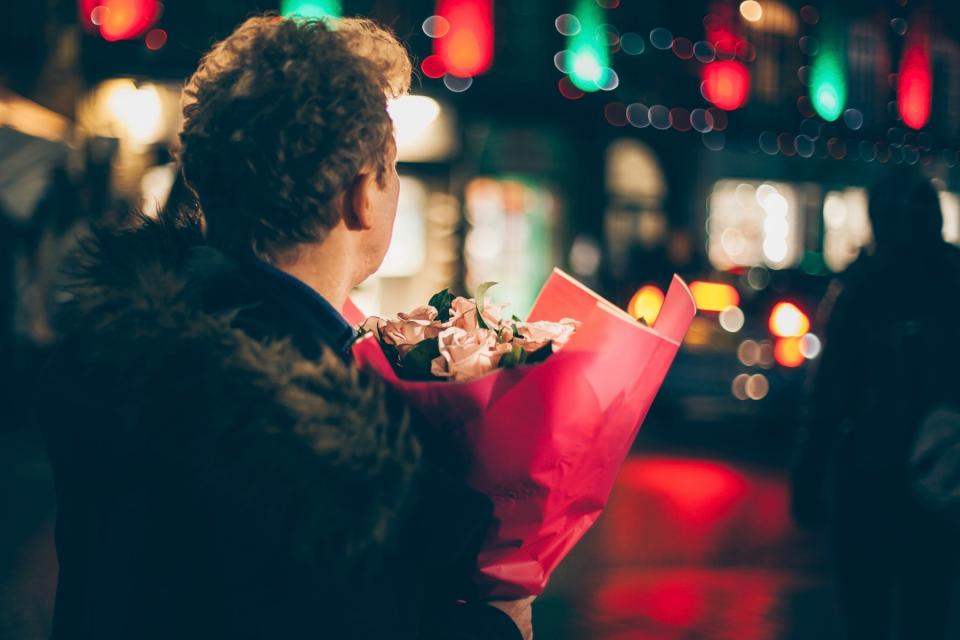 Man carries a bouquet of flowers on the street.
