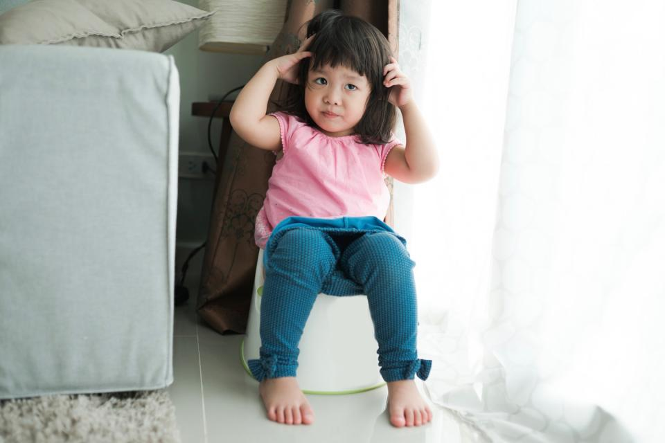 Young girl sits on a potty training toilet.