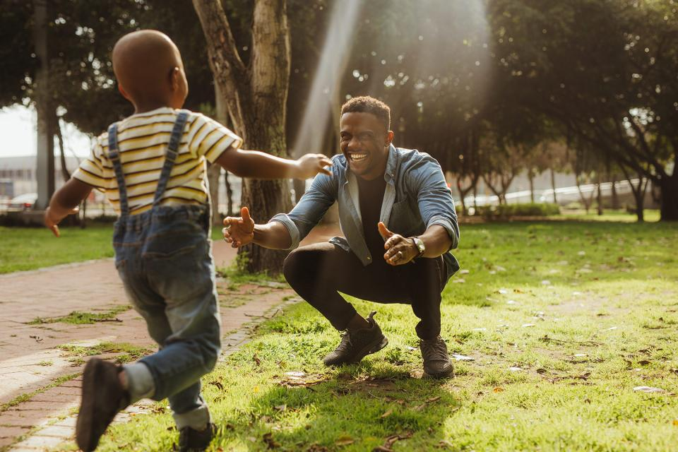 Young boy runs into his smiling father's arms on a clear spring day